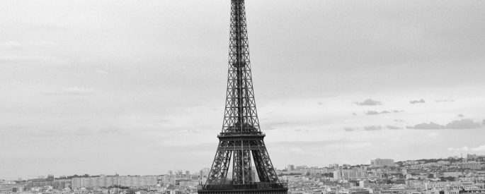 a black and white photograph of the Eiffel Tower standing over Paris