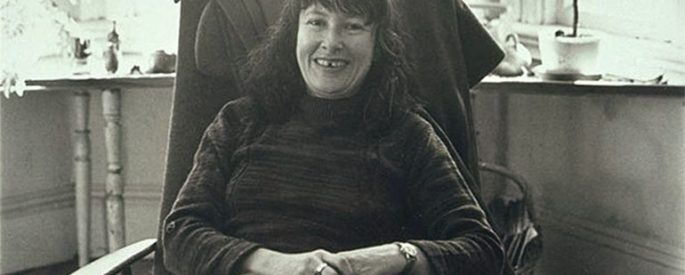 black and white image shows the poet Denise Levertov seated in an armchair and smiling