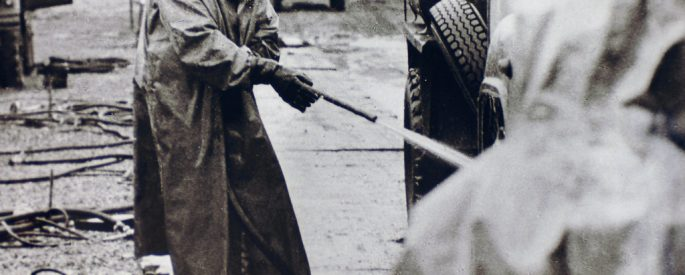 historical black and white photograph of a a figure in a hazmat suit spraying the wheels of a car out of frame with a hose - other people in the photograph are also wearing hazmat suits, the images comes from a collections of the Chernobyl accident from the Ukrainian Society for Friendship and Cultural Relations with Foreign Countries