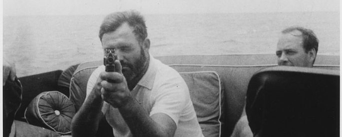 black and white photo of Hemingway pointing a gun at the taker of the photograph, the gun covering half of his face - he sits aboard a boat, accompanied by a male friend