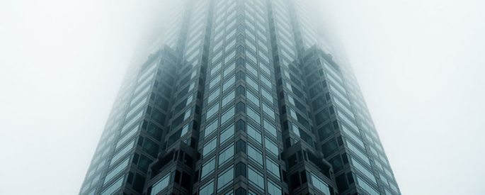 photograph of a high rise, glass building taken from below - the building stretches high up into a cloudy, foggy, gray sky, obscuring the top of the building