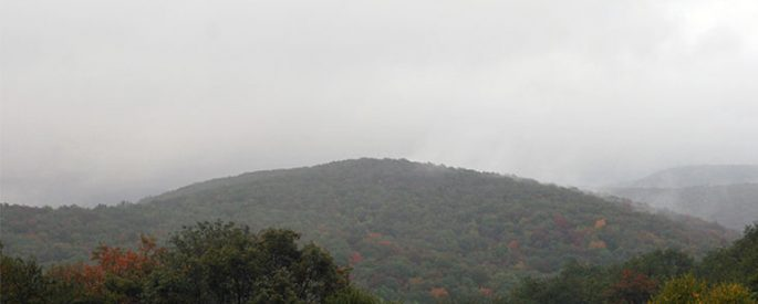 landscape photograph of the Blue Ridge Mountains covered in fog--there is a gray sky, and the mountains are dotted with autumn foliage