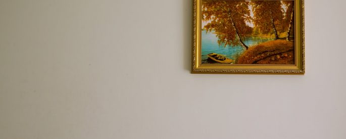 a single painting of a boat on a lake shaded by autumn trees in a gold frame hangs on a bare, beige wall