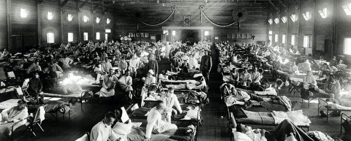 a black and white photograph of a makeshift hospital interior--rows and rows of hospital beds contain some patients who are sitting up in their beds and nurses in old, white nurse uniforms weaving throughout the rows of beds