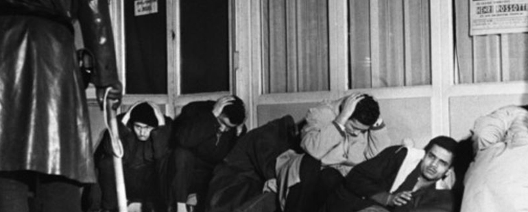 black and white photograph of protestors during the 1961 Paris protests against a storefront, crouching and covering their heads--the left side of the photograph a figure in a leather trench coat holds a club