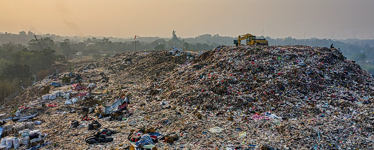 a bird's-eye photograph of a massive pile of trash, to the right hand side construction equipment sits idle; the beyond the pile is a foggy jungle