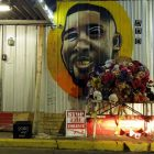 "a mural of Alton Sterling on the white-gray walls of a building; beneath is a stand with a pile of bouquets of flowers and stuffed animals, a pair of headlights shine off the base of the wall next to a sign that, in white and red lettering reads, ""STOP THE VIOLENCE"" with an illustration of a gun"