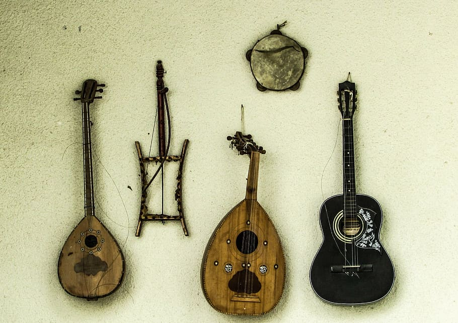 two wooden ouds hang against a pale green wall alongside a black ukulele