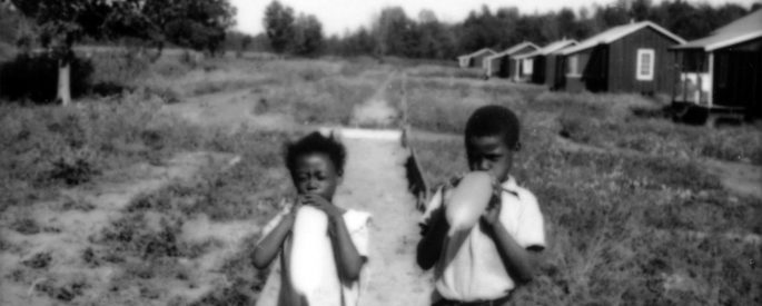 1937, black and white photograph by Louise Boyle of two young Black children blowing up balloons