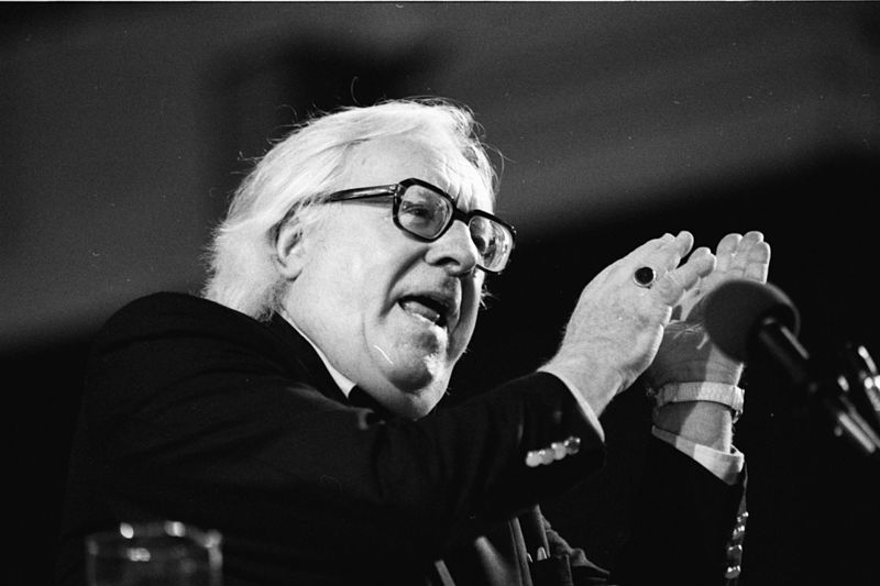 black and white photograph of Ray Bradbury, speaking at a microphone, with his hands gesturing upwards as he speaks