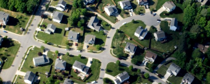 photograph of a sprawling suburb at an aerial view--houses connected by winding roads against bright green grass
