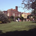 a film photograph of the back of the Lamb House--a small family appears to be playing on the lawn