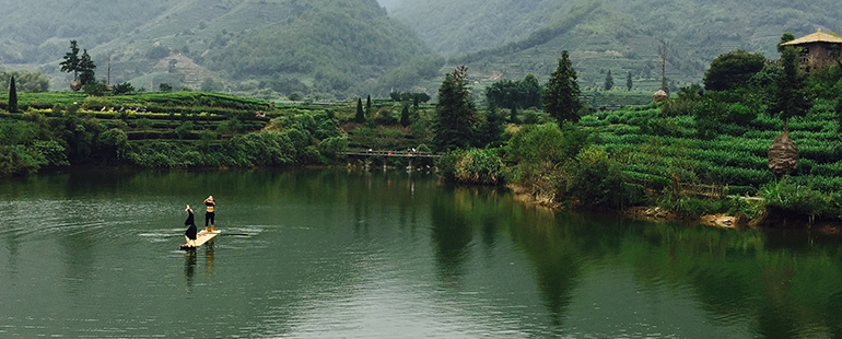 a photo taken by the author of this piece, image of a peaceful lake with two figures on a board in the middle of the lake--it is surrounded by mist colored mountains and lush landscapes
