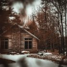 photograph of a cabin in snowy woods, the photo seems to be taken through the trees