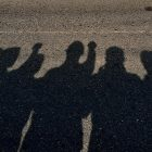 "photo titled ""Shadows of comrades at Kannur"" depicts the shadows of a group standing side by side with fists raised"