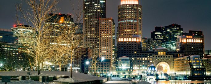photo of the Boston skyline taken at night in the snow