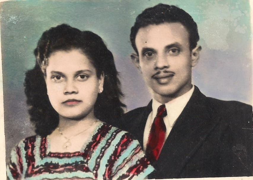 """the photo the writer describes in the piece in which the writer's grandmother """"stands beside my grandfather. Both of them wear Western clothing, my grandfather a black suit with a red tie and my grandmother a blue dress with red embroidery. Their outfits look painted onto them, the clashing hues seeping into each other like watercolor"""""""