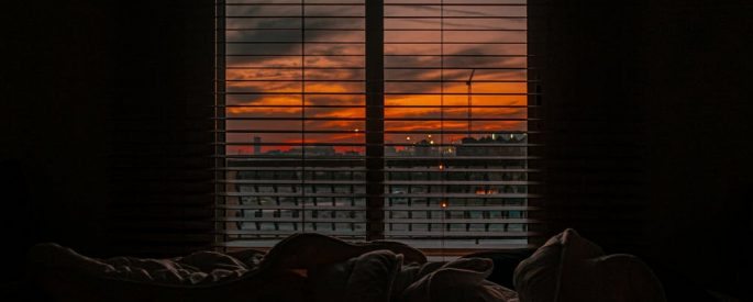 image of a crumpled bed sheet in front of a a window--the sun is rising outside