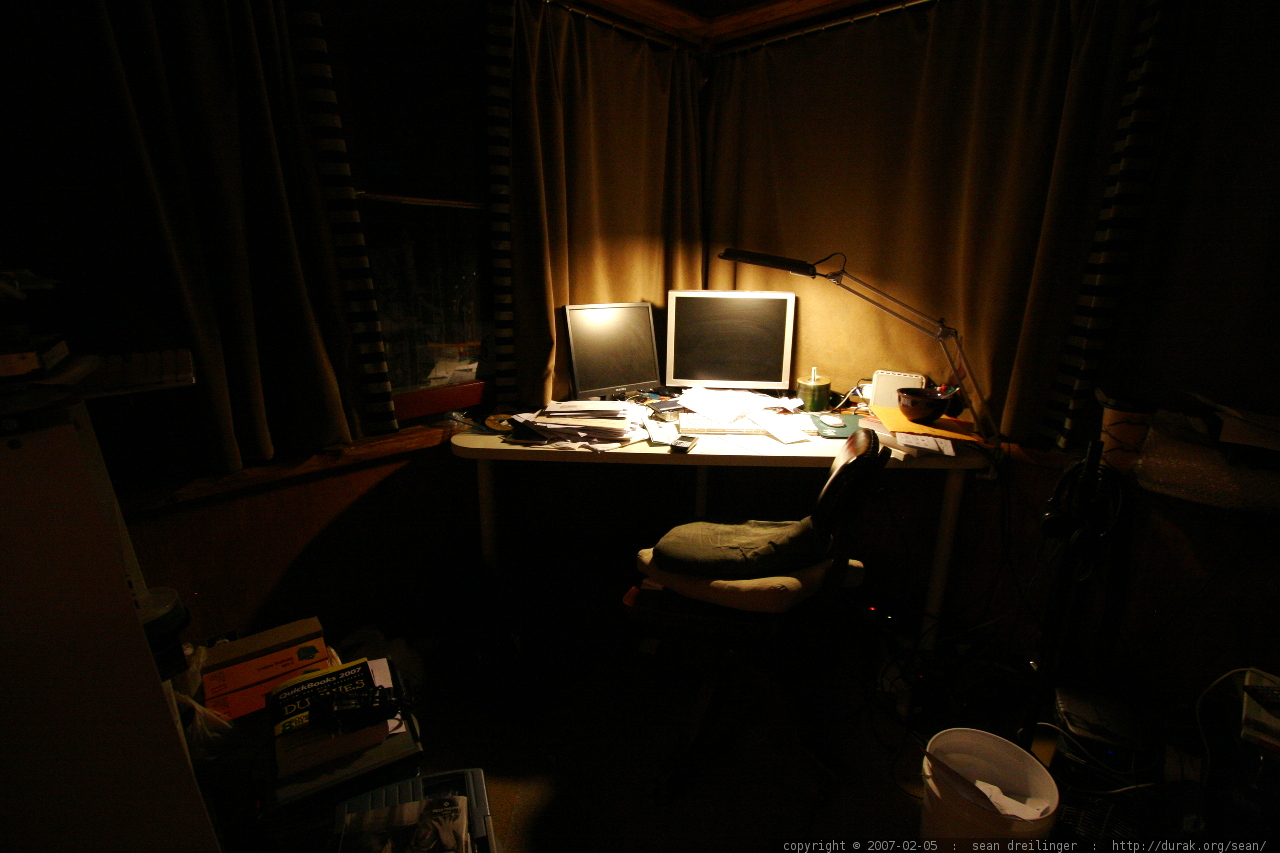 photo of a messy desk illuminated only by a small lamp